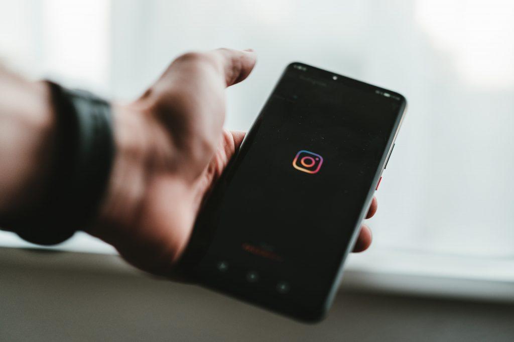 Photo d'une main d'homme tenant un téléphone portable avec le logo Instagram, illustration pour les conseils Instagram