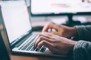 Cette image représente les mains d'un homme entrain de taper sur un clavier pour créer un site wordpress.