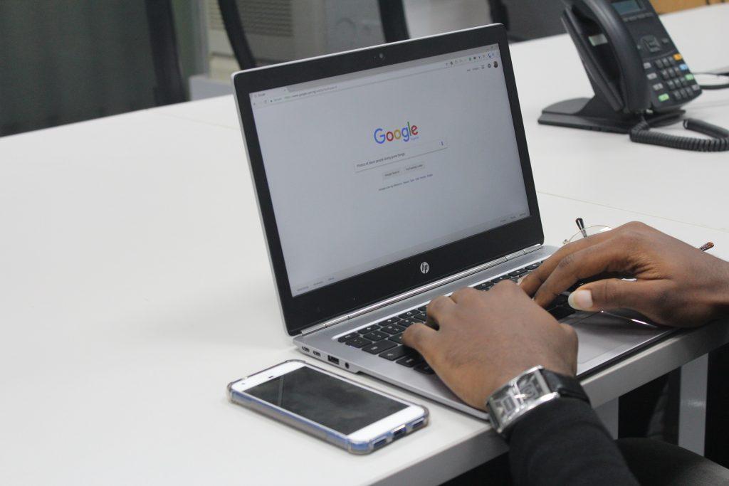 Photos de mains en train de faire une recherche Google - illustration pour l'article de blog concernant la balise meta description