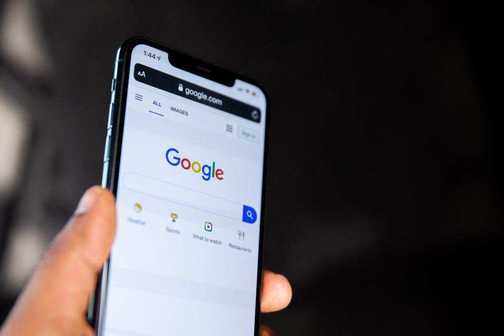 Image d'un téléphone dans les mains affichant la page Google. Image pour illustrer l'article de blog concernant le cache de navigateur